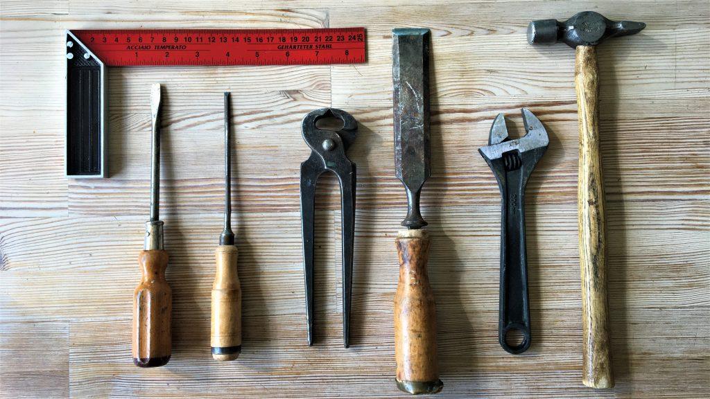 Verktyg ur en verktygslåda. Vinkelhake, skruvmejslar, tång, stämjärn, skiftnyckel och hammare